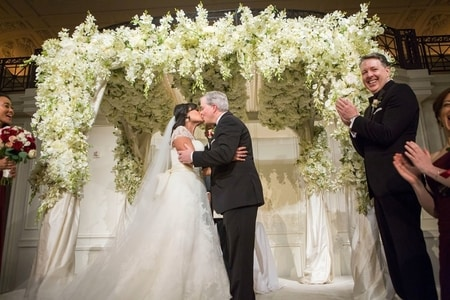 Kristen Welker and John Hughes kissing each other at their wedding