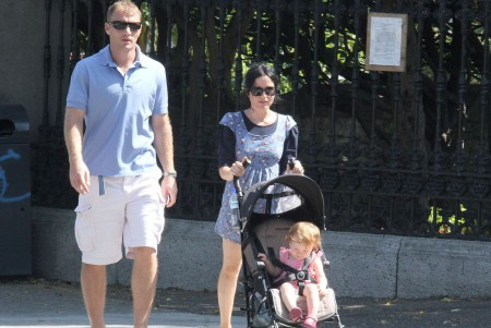 Andrea Corr and Bret Desmond with their child on the street of London