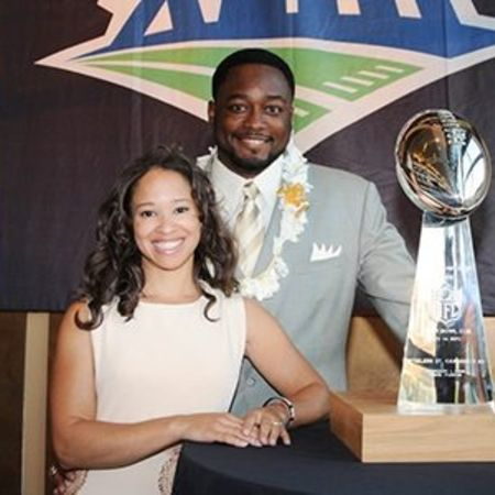 Mike and Kiya posing for a picture in front of trophy earned by Mike Tomlin.