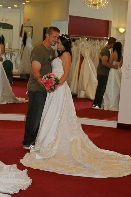 Stephanie Hayden in her wedding dress and Kris Ford holding her hand