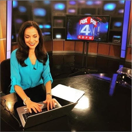 Natalie Solis working at her desk in the Fox 4 Newsroom