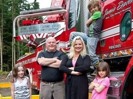 Adam Gazzola and Lucy Austin with their three children in front of a truck