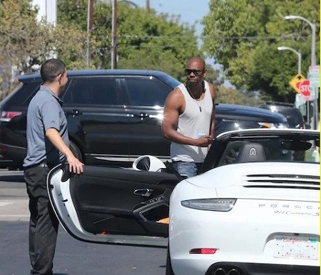Dave Chappelle getting inside his Porsche sports car