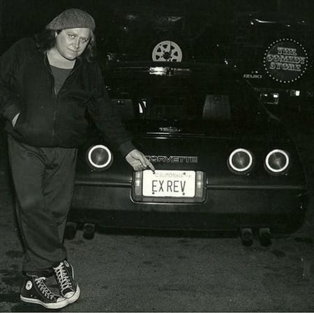 Sam Kinison showing his car in the photo