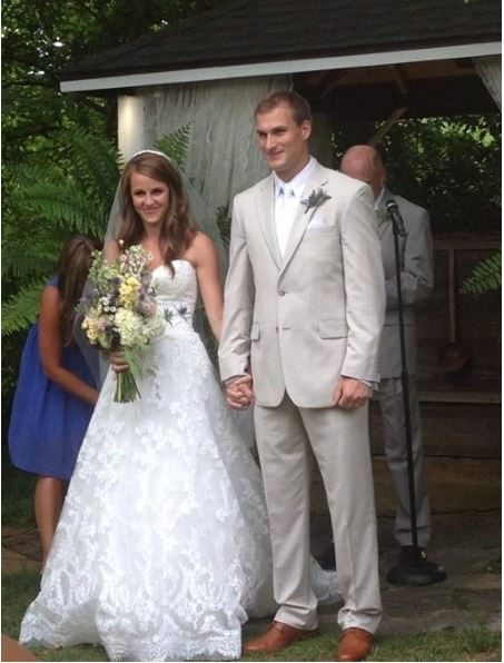 Kirk Cousins holding his wife's hand Julie Hampton at their wedding