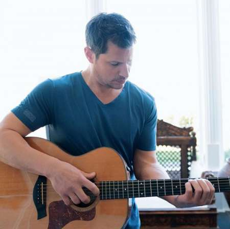 Nick practicing his song in an acoustic guitar. Know more about Nick Lachey age, net worth, parents, family, brother, siblings, marriage, wife, children, songs and many more