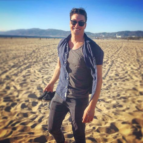 Daniel Lissing posing barefoot on sand larger surfaces
