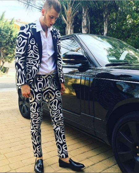 MIllionaire musician, Machine gun kelly wearing black & white suit and driving expensive thousand dollar car. He is living a lavish lifestyle in rich manner.