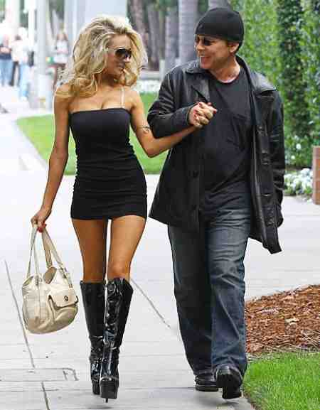 Courtney Stodden and Doug Hutchison holding hands while walking on the street