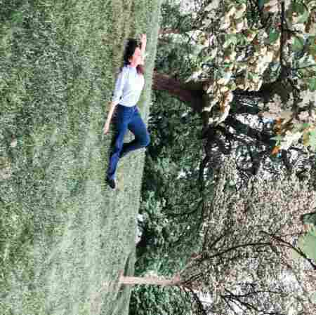 Aishah Hasnie lying down on the grass, experiencing the joy of nature