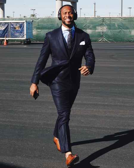 Larry Fitzgerald is walking in Seattle, Washington wearing dark blue tuxedo and a check tie with a white undershirt