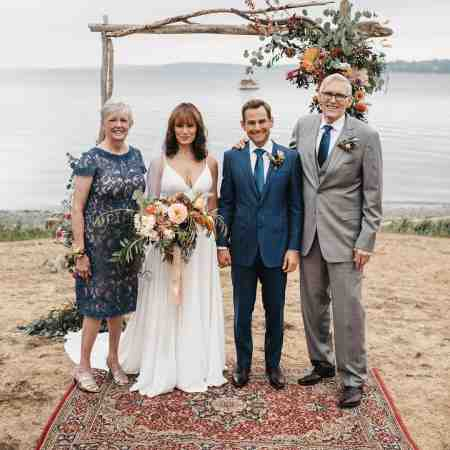 Emily Swallow and her husband, Chad Kimball standing alongside her parents. Explore more about the couple's married life.