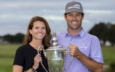 Maggie holding the trophy with her golfer spouse, Robert.